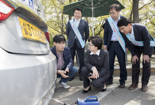 Environment Minister Kim Eun-kyung (center, first row) observes vehicle emissions testing near the Sports Complex Station in Jamsil southeastern Seoul on April 20, which is designated as free emissions checkup day here. (Yonhap)