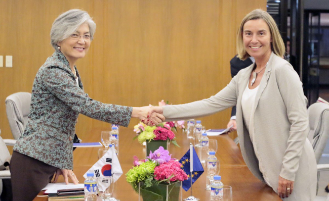 South Korean Foreign Minister Kang Kyung-wha (left) and Federica Mogherini, the European Union's high representative for foreign affairs and security policy, shake hands before a meeting in Manila in August last year.
