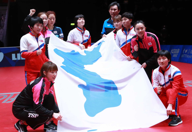 In this photo from May 4, 2018, members of the unified Korean women's table tennis team hold up the Korean Unification Flag after losing to Japan in the semifinals of the World Team Table Tennis Championships at Halmstad Arena in Halmstad, Sweden. (Yonhap)