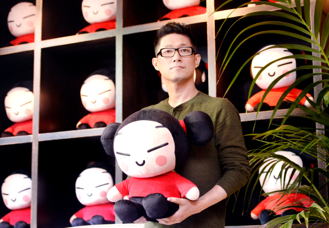 Art Director Kim Boo-kyoung poses with a Pucca doll at Puccafe in southern Seoul. (By Park Hyun-koo / The Korea Herald)