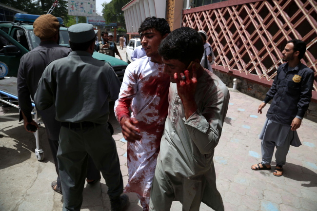 A man who was wounded in a bomb blast reacts at the scene of an attack in Jalalabad, Afghanistan, 13 May 2018. as fighting between the security forces and militants continue. (Yonhap)