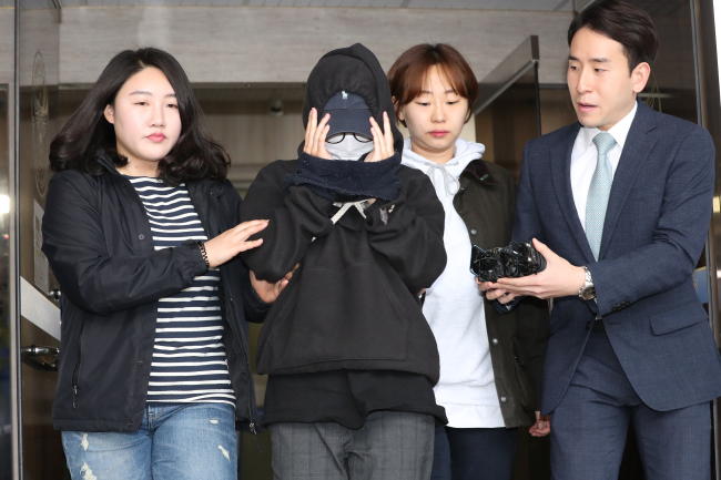A female model (second from left) is being questioned by reporters afterbeing grilled by policefor leaking a nude photograph of her male colleague at a police station in Seoul on Saturday. She was eventually brought into custody. (Yonhap)