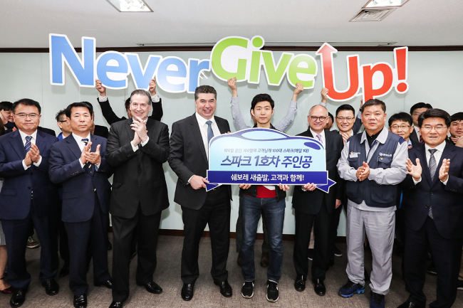 GM Korea Vice President Dale Sullivan (third from left), GM Korea CEO Kaher Kazem (fourth from left), GM Executive Vice President Barry Engle (sixth from left) and GM Korea's union chief Lim Han-taek (seventh from left) delivered the Chevy Spark compact car to the first winner of the promotion event Park Jae-seok (fifth from left) at GM Korea headquarters on Monday. (GM Korea)