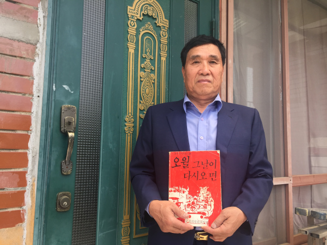Kim Dae-yoon poses with a book that contains photographs of victims during the 1980 Gwangju Democratization Movement, which he purchased a few days after the 10-day deadly crackdown, in front of his home house in Gwangju, Monday. (Claire Lee/The Korea Herald)