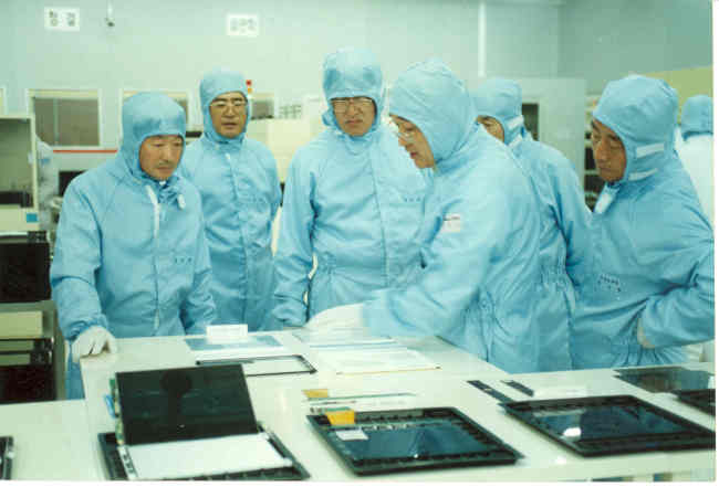 Koo (far left) inspects products at LG Display's liquid-crystal display production line in October 1996. (LG)
