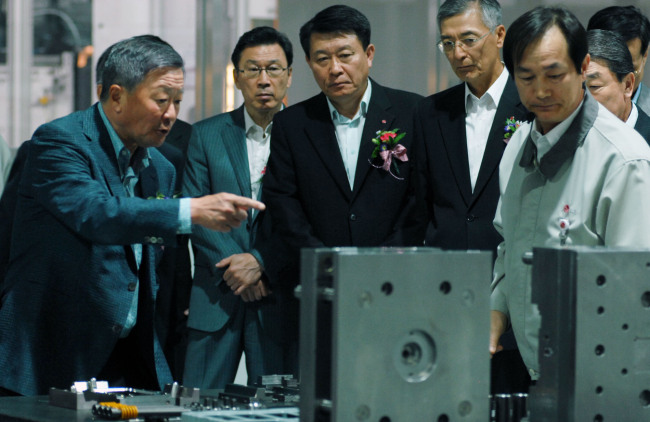 Koo (far left) looks around LG Electronics' Mold Technology Center on its groundbreaking day in April 2012. (LG)