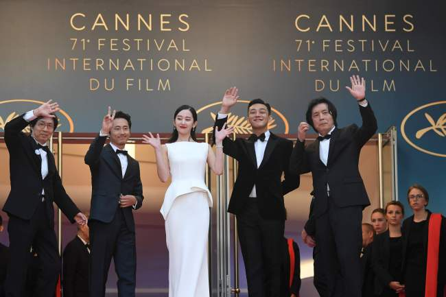 """From left: Producer Lee Joon-dong, actors Steven Yeun, Jeon Jong-seo, Yoo Ah-in, and director Lee Chang-dong of """"Burning"""" pose for photos at the 71st Cannes Film Festival in France on Wednesday. (Yonhap)"""