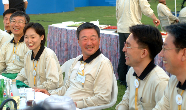 The late LG Group Chairman Koo Bon-moo (center) speaks with company employees back in May 2002. (LG Group)