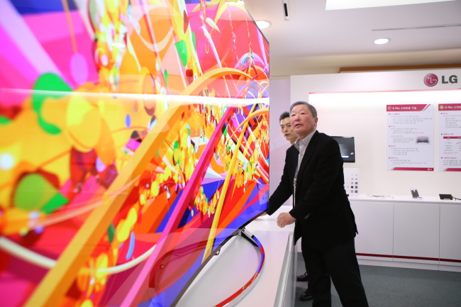 Koo Bon-moo, the late chairman of LG Group, inspects an organic light-emitting diode television at a R&D performance briefing in March 2014. (LG Group)