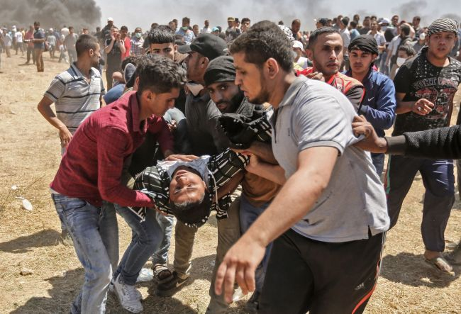 Palestinian protesters carry an wounded person during the May 14th protest that marked the 70th anniversary of the 1948 Nakba catastrophe denounced the relocation of the US Embassy to Jerusalem. (Yonhap)