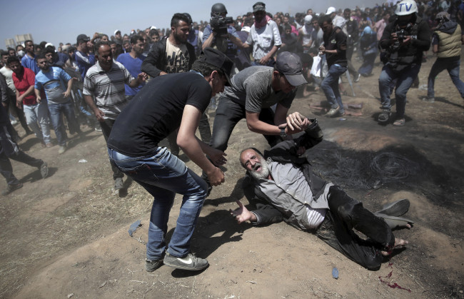 In this May 14, 2018 file photo, an elderly Palestinian man falls on the ground after being shot by Israeli troops during a deadly protest at the Gaza Strip's border with Israel, east of Khan Younis, Gaza Strip. The modern Middle East has been plagued by ruinous wars: country versus country, civil wars with internecine and sectarian bloodletting, and numerous eruptions centered in the Israeli-Palestinian conflict. But never in the last 70 years have they seemed as interconnected as now with Iran and Saudi Arabia vying for regional control, while Israel also seeks to maintain a military supremacy of its own. (AP/Yonhap)