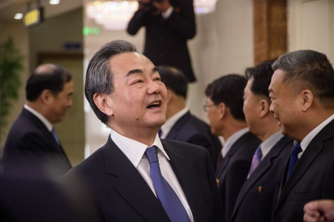 Chinese Foreign Minister Wang Yi greets North Korean officials in Pyongyang on May 2. (Yonhap)
