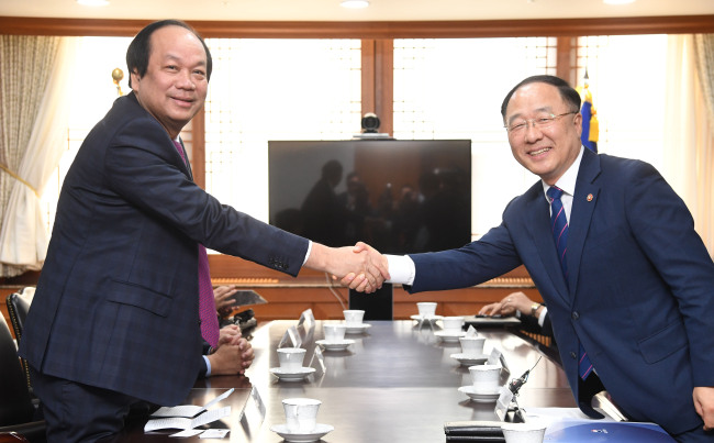 Government Policy Coordination Minister Hong Nam-ki (R) shakes hands with Mai Tien Dung, minister and chairman of Vietnam`s Government Office, during a meeting in Seoul on May 23, 2018. (Yonhap)