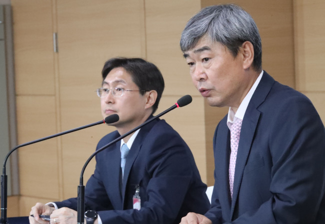 Yoo Chang-jo (right), chairman of the government task force for improving the duty-free shop system, presents an alleviated business licensing plan at a press briefing Wednesday. (Yonhap)