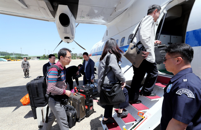 South Korean journalists board a plane at Seoul Airport in Seongnam on Wednesday, heading to North Korea to cover the dismantlement of the North`s key nuclear test site. (Yonhap)