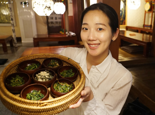 The Korea Herald`s reporter Im Eun-byel holds up a basketful of namul (Lim Jeong-yeo/The Korea Herald)