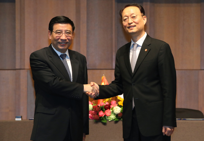 South Korean Trade, Industry and Energy Minister Paik Un-gyu (R) shakes hands with Chinese Industry and Information Technology Minister Miao Wei prior to their talks at a Seoul hotel on May 24. (Yonhap)