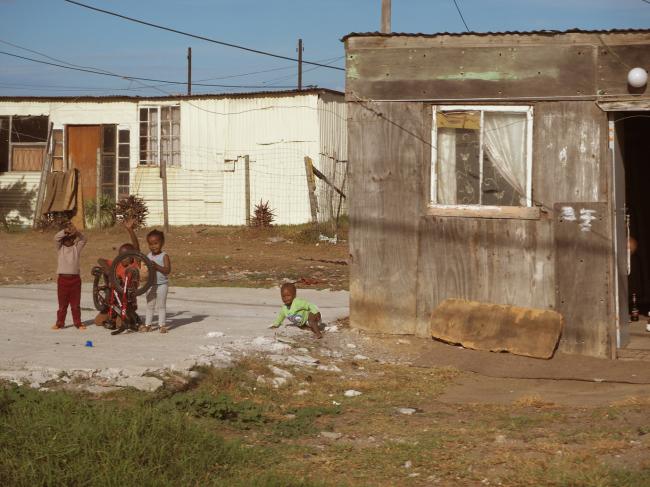 Children play in front of a decrepit house in a Port Elizabeth township. (Joel Lee/The Korea Herald)