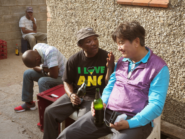 A resident of a Port Elizabeth township and Korean tourism magazine journalist talk over beer at a shebeen. (Joel Lee/The Korea Herald)