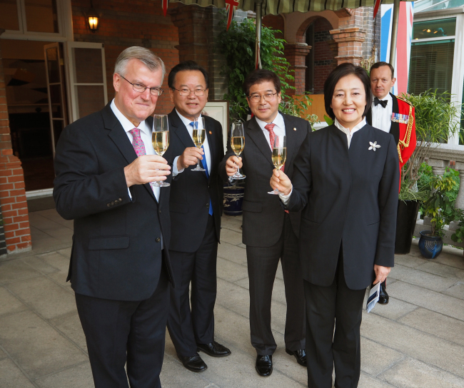 British Ambassador to Korea Simon Smith (left) raises a glass with Democratic Party Rep. Park Young-sun, who heads the Korea-UK parliamentary friendship group; Rep. Kim Seang-tae of the Liberal Korea Party (second from right); and Interior and Safety Minister Kim Boo-kyum, at the Queen Elizabeth's 92nd birthday party reception at the envoy's residence in Seoul on Thursday. (Joel Lee/The Korea Herald)