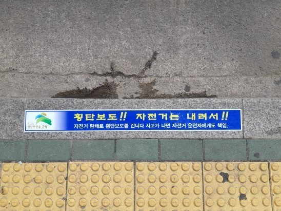 """A warning sticker on the side of a pedestrian crossing in Yeokchon-dong, Eunpyeong-gu, Seoul, says """"Get off your bike."""""""