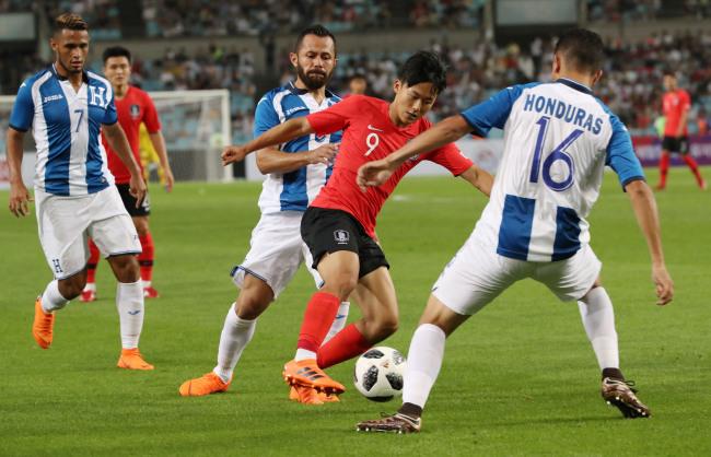 South Korea`s Lee Seung-woo (C) dribbles against Honduran players during a friendly match between South Korea and Honduras at Daegu Stadium in Daegu on May 28. (Yonhap)