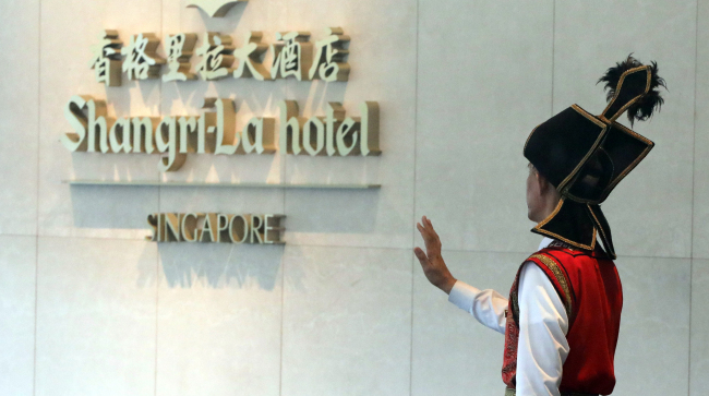 A hotel employee hails a cab at the Shangri-La Hotel in Singapore. (Yonhap)