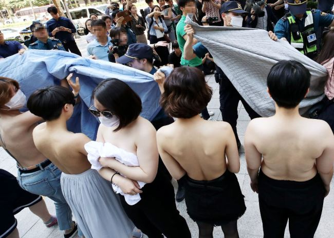 Activists from feminist group Fire Femi Action protest topless against Facebook's sexually discriminatory policy, in front of Facebook Korea in Gangnam, Seoul, Saturday. (Yonhap)