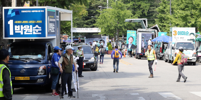 Canvassing trucks are parked in front of the entrance to the Dobongsan trail in Seoul on Sunday. (Yonhap)
