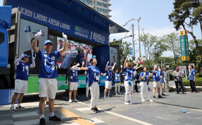 Election campaign workers dance in front of a canvassing truck parked near Sindorim Station in Seoul on Sunday. (Yonhap)