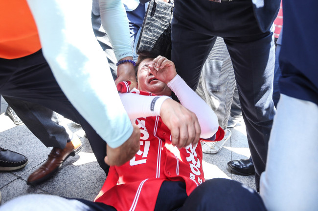 Rep. Kwon Young-jin of the Liberty Korea Party falls down after being pushed by a protestor during a political campaign Thursday in Chuncheon, Gangwon Province. Yonhap