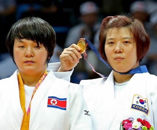 In this file photo taken on Sept. 22, 2014, South Korea`s Jeong Gyeong-mi (right) shows her gold medal after beating North Korea`s Sol Kyong in the women`s under-78-kilogram judo event at the Asian Games in Incheon. (Yonhap)