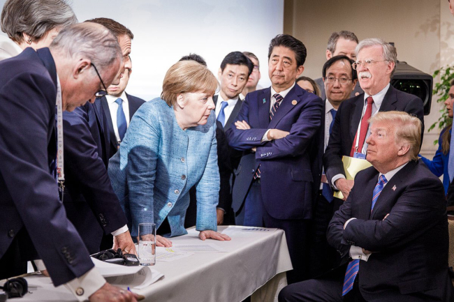 German Chancellor Angela Merkel speaks to US President Donald Trump during sideline discussions on Day 2 of the G7 Summit in La Malbaie, Quebec, Canada, on June 9, 2018. (UPI-Yonhap)