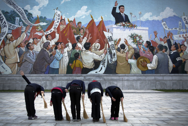 School girls holding brooms bow to pay their respects toward a mural that depicts the late North Korean leader Kim Il-sung delivering a speech, before sweeping the area surrounding the mural. (AP)