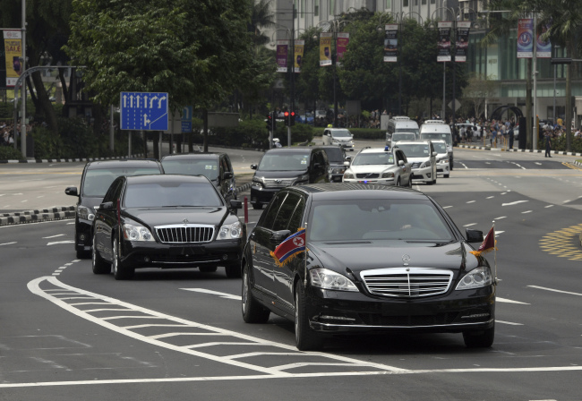 The North Korean motorcade, believed to be carrying North Korean leader Kim Jong-un, travels along Singapore's Orchard Road. (AP-Yonhap)