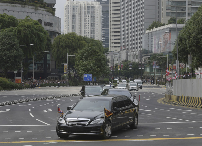 The North Korean Motorcade carrying Kim Jong Un travels past Singapore's Orchard Road on its way to the St Regis Hotel Sunday. (AP-Yonhap)