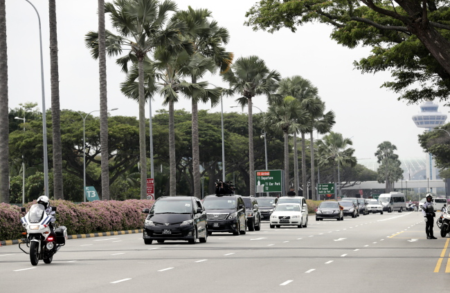 The motorcade carrying North Korean leader Kim Jong-un heads into the city out of the airport after he touched down in Singapore. (EPA-Yonhap)