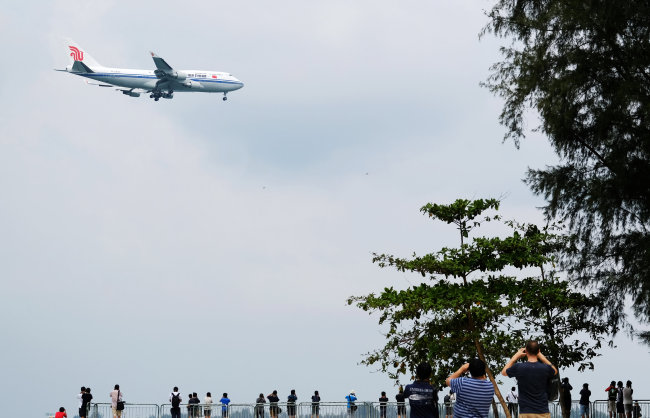 People in Singapore take pictures of the Air China carrier believed to be carrying North Korea's leader Kim Jong-un as it approaches to land. (Reuters-Yonhap)