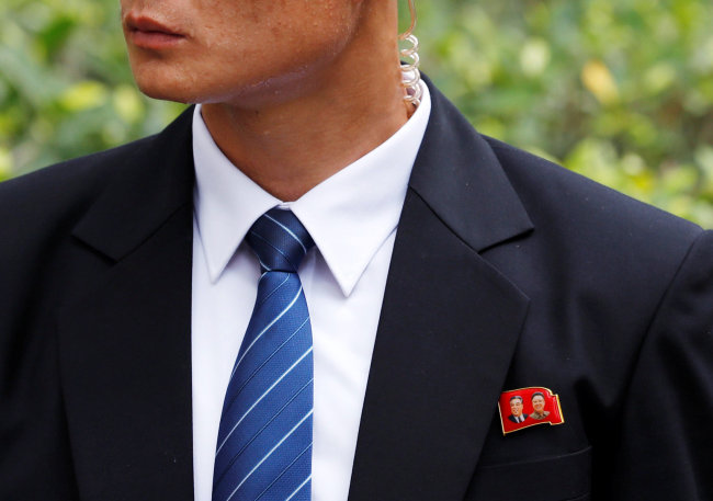 A member of the North Korean security personnel wears a pin as he waits for the arrival of North Korea's leader Kim Jong-un at St Regis hotel in Singapore. (Reuters-Yonhap)