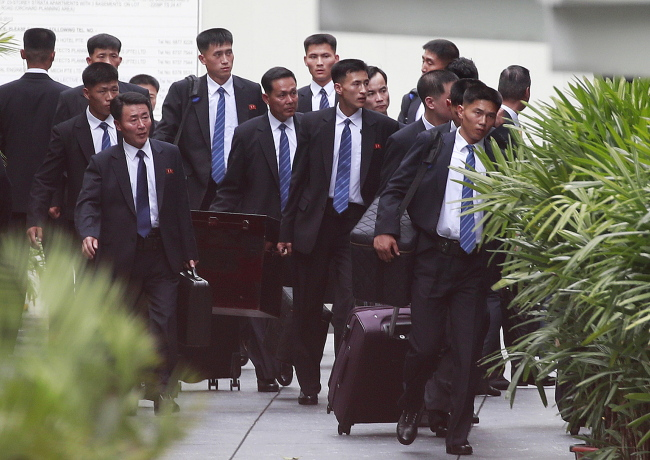North Korean security personnel arrive at the St Regis hotel, where North Korean leader Kim Jong-un will stay, ahead of his expected arrival. (EPA-Yonhap)