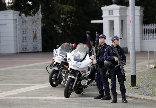 Singaporean Police officers stand guard in front of the Istana Presidential Palace, where North Korean Leader Kim Jong-un and Singapore Prime Minister Lee Hsien Loong will meet. (EPA-Yonhap)