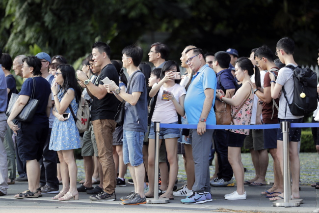 Singaporeans gather in front of the Istana Presidential Palace. (EPA-Yonhap)