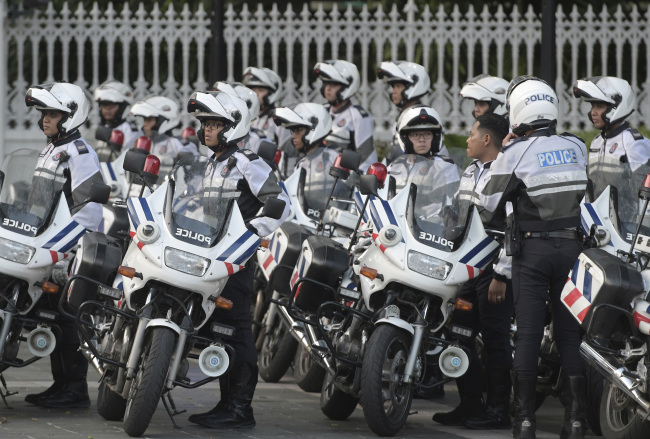 Police officers escorting the motorcade of North Korea leader Kim Jong-un park after he arrives at the Istana, or Presidential Palace, in Singapore. (AP-Yonhap)
