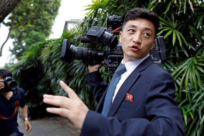 A North Korean cameraman reacts as he is chased by media outside St Regis hotel. (Reuters-Yonhap)
