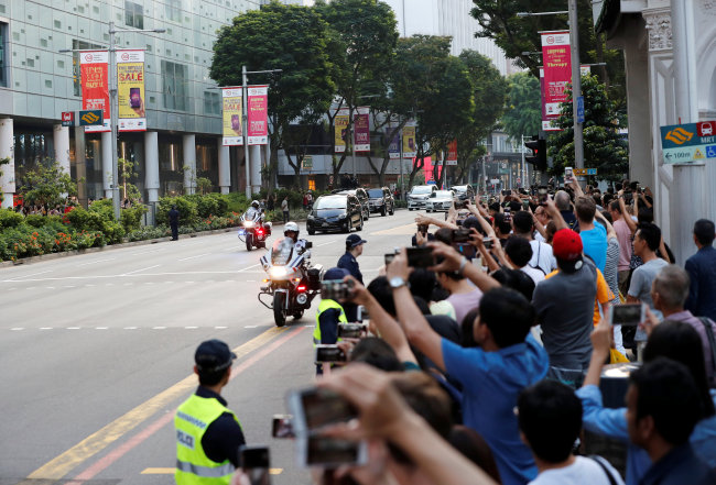 People take photographs while police vehicles escort the motorcade of North Korean leader Kim Jong-un as it makes its way to the Istana. (Reuters-Yonhap)
