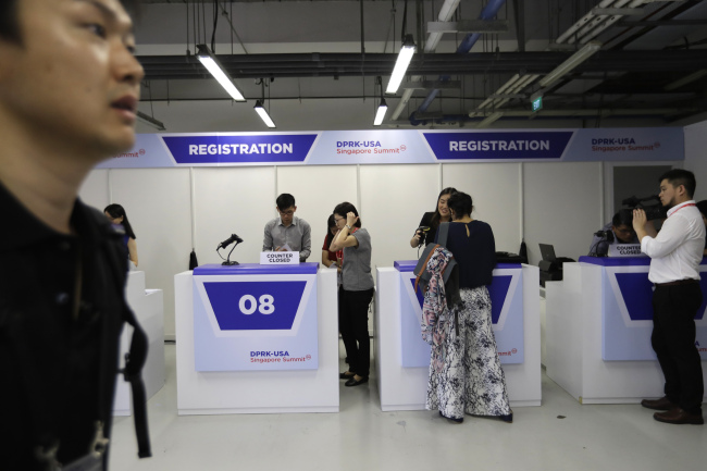 Members of the press are seen collecting their accreditation at the media center. (AP-Yonhap)