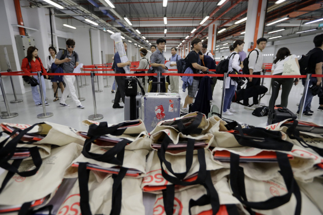 Members of the press stand in line to collect their accreditation at the media center. (AP-Yonhap)