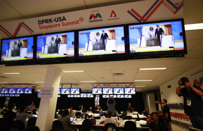 People look at US President Donald Trump's arrival at the airport on tv screens in the International Media Centre. (EPA-Yonhap)