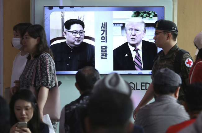 Viewers look on at a TV screen showing file footage of US President Donald Trump (right) and North Korean leader Kim Jong Un during a news program at Seoul Railway Station in Seoul on Monday. (AP-Yonhap)