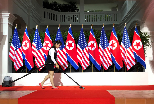 A worker vacuums the stage at the spot where US President Donald Trump and North Korea`s leader Kim Jong-un are expected to meet and shake hands for the first time at the start of their summit at the Capella Hotel (Reuters)